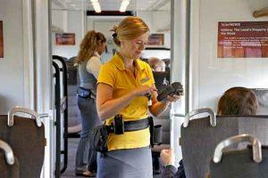 Petugas kondektur memeriksa tiket dengan perangkat scan RFID.